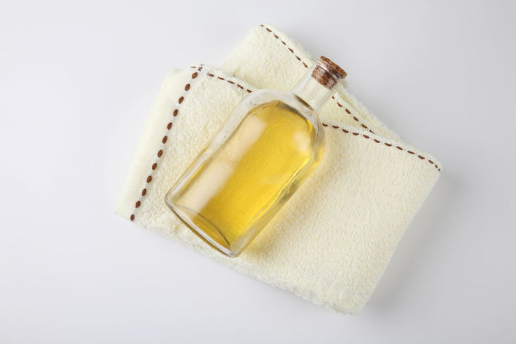 High angle view of towel with oil in bottle over white background