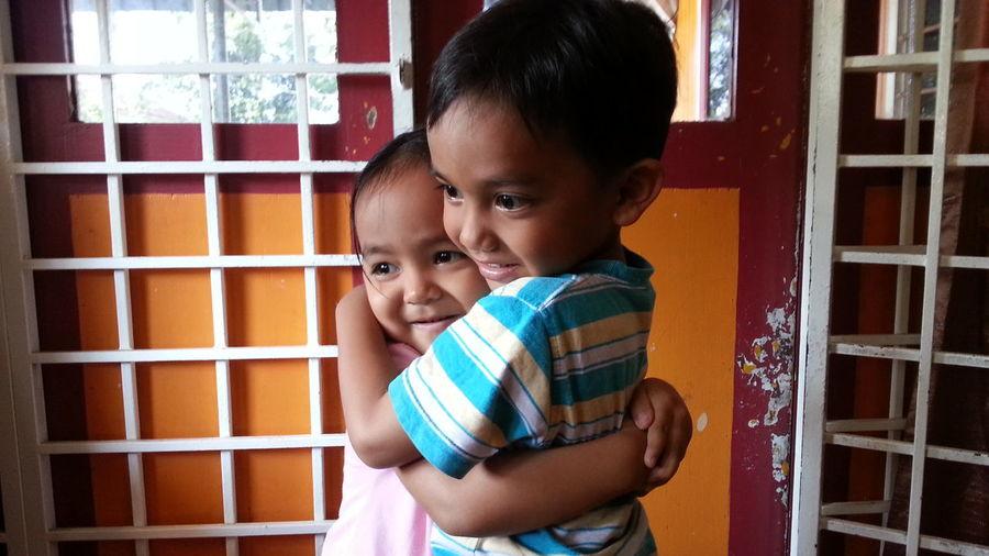 Happy siblings hugging at home