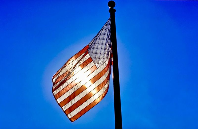backlight of a USA flag Backlight Stars And Stripes Flag Icon Iconic Stripes Pattern Blue Color Representation Pride Honor Old Glory Analog Photography Day Daylight Day Light Outdoors Horizontal Blue Sky Patriotism Low Angle View Clear Sky No People Copy Space Pole Independence Freedom Emotion Striped Wind National Icon