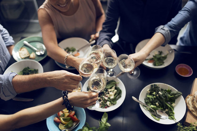 Midsection of people holding drink served on table
