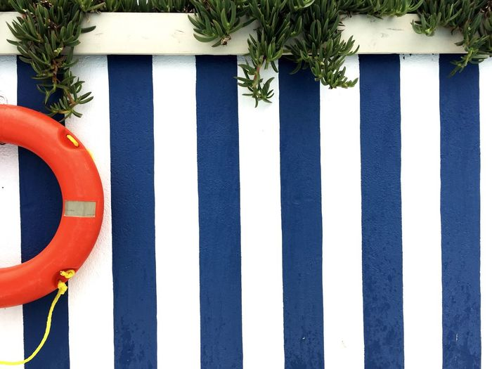 Lifeguard ring on striped fence