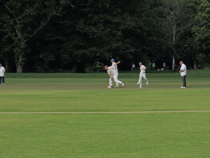 Cricket Field Adult Adults Only Cricket Match Day Golf Golfer Grass Green Color Leisure Activity Men Nature Outdoors People Playing Real People Sport Sports Uniform Sportsman Standing Togetherness Tree Young Adult