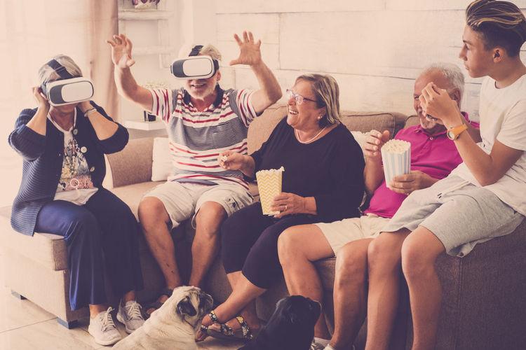 Happy Family Enjoying While Sitting On Sofa At Home