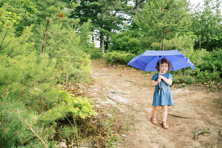 Full length of man holding umbrella against trees
