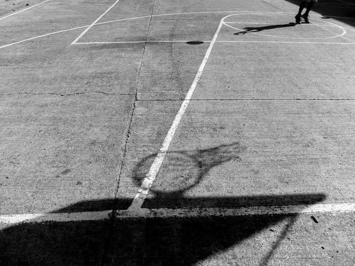Shadow of basketball hoop on court