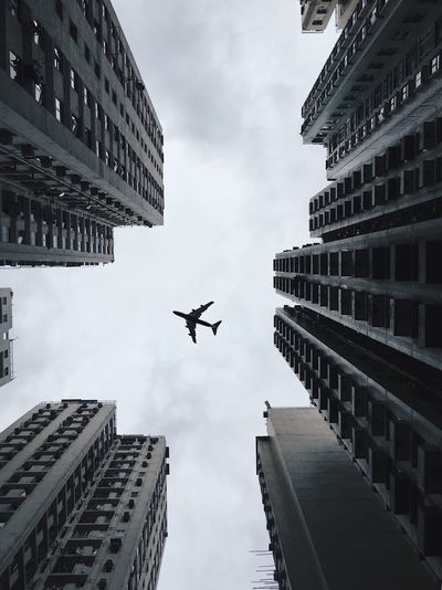 Directly below shot of airplane flying against sky in city