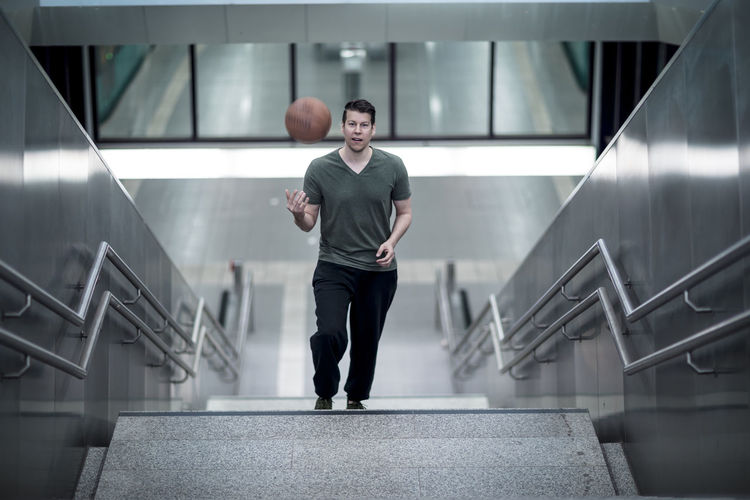 High angle portrait of young man with basketball moving up on steps