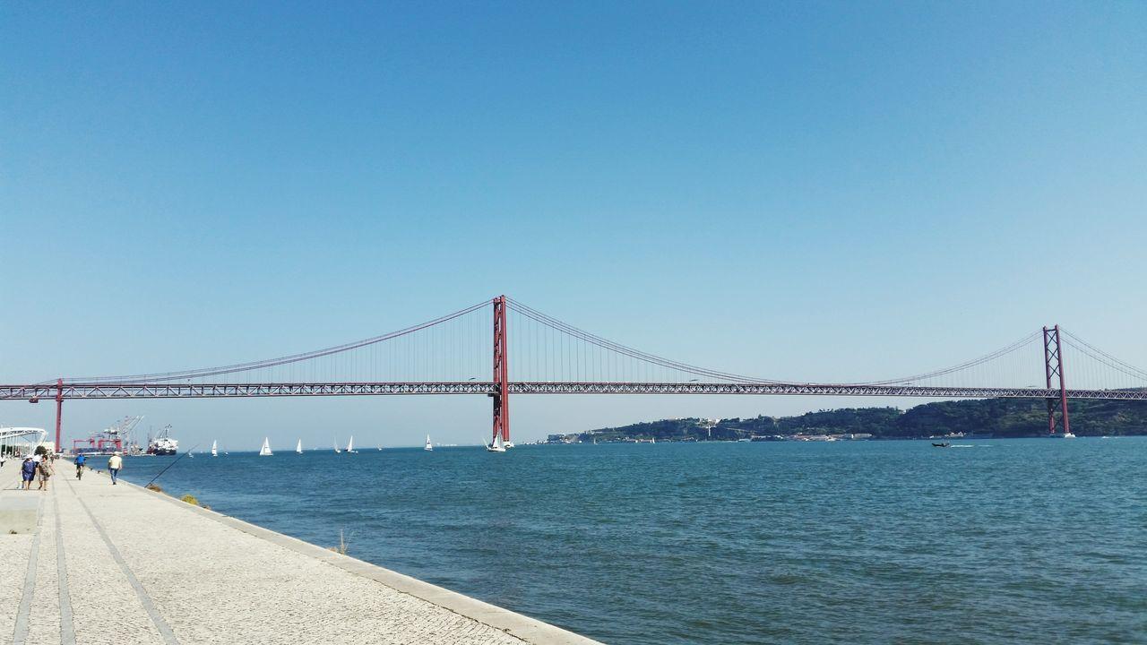 25 De Abril Bridge Over Tagus River Against Clear Blue Sky