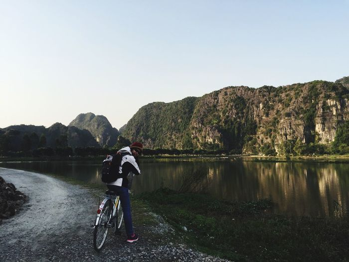 Rear view of woman with bicycle on riverbank against clear sky