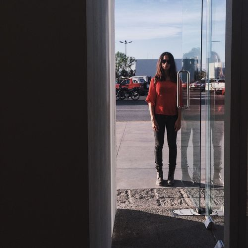 Full length of woman standing by glass door in city