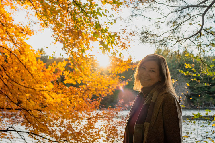 Portrait of woman standing by tree during autumn