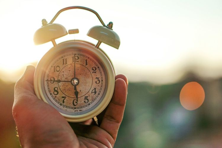 Close-up of hand holding alarm clock against clear sky