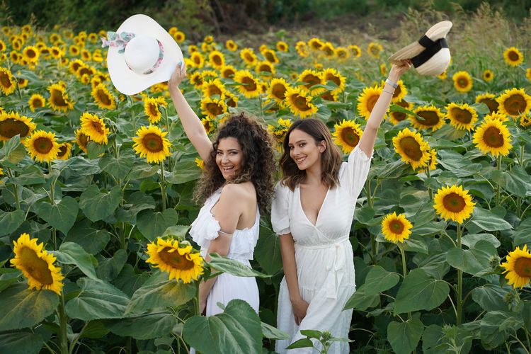 Portrait of female friends standing amidst sunflowers