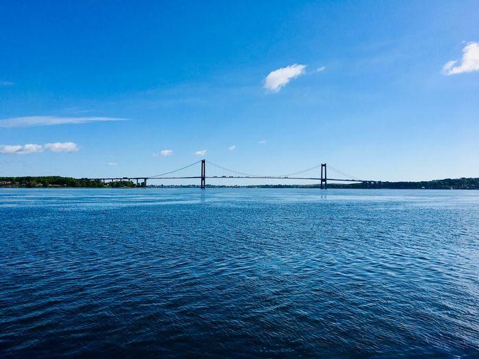 Bridge over calm sea against blue sky