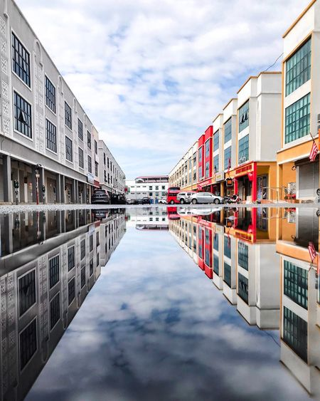Reflection of buildings in canal against sky