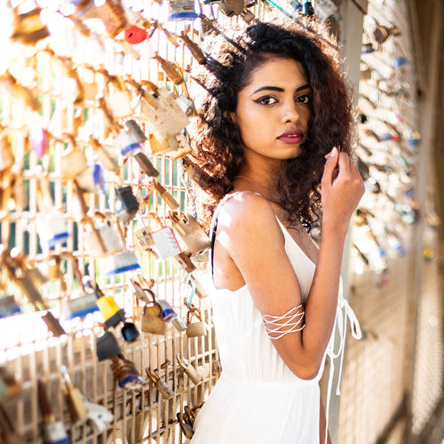 Portrait of young woman standing by padlocks
