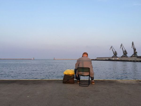 Lonely Angler - Gdynia 12 September 2016 ( IPhone 6+ ) Angler Beauty In Nature Clear Sky Cranes And Construction EyeEm Best Edits EyeEm Best Shots Fisherman Gdynia Harbour Horizon Over Water Nature Nostalgic  One Man Only One Person Outdoors Poland Rear View Scenics Sea Senior Adult Sitting Street Photography Streetphotography View Water