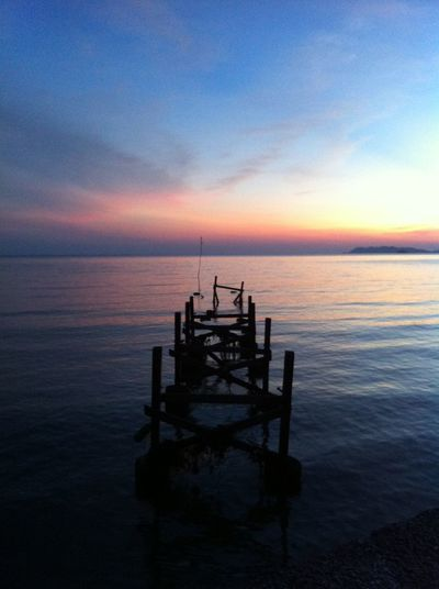 Silhouette wooden posts on sea against sky during sunset