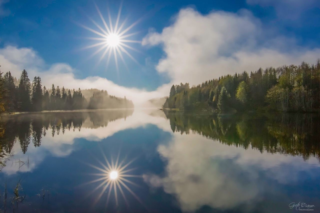 reflection, sky, water, beauty in nature, nature, cloud - sky, lake, tranquil scene, tranquility, scenics, sunlight, waterfront, idyllic, tree, outdoors, sun, no people, day