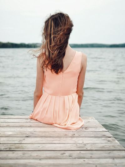 Rear View Of Woman Sitting On Pier Over Lake