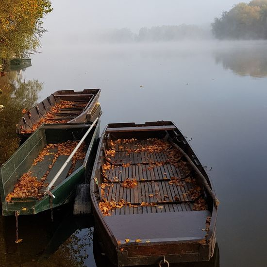 High angle view of boats moored in lake during foggy weather