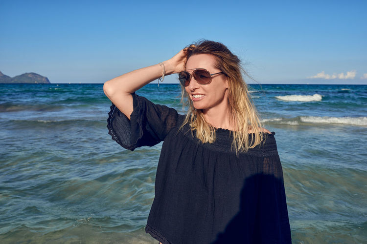 Happy attractive blond woman at the seaside Copy Space Travel Woman Beach Best Ager Clear Sky Day Front View Horizon Over Water Leisure Leisure Activity Lifestyles Middle-aged Nature One Person Outdoors Real People Sea Smiling Standing Summer Sunglasses Vacation Water