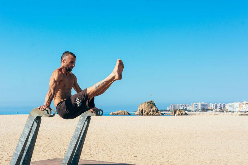 Full length of shirtless man on beach against clear blue sky