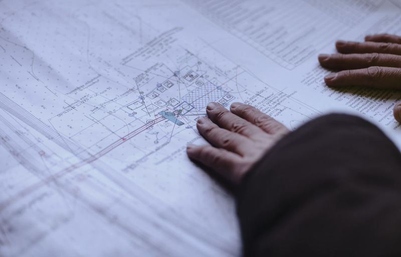 Close-up of engineer working touching blueprint