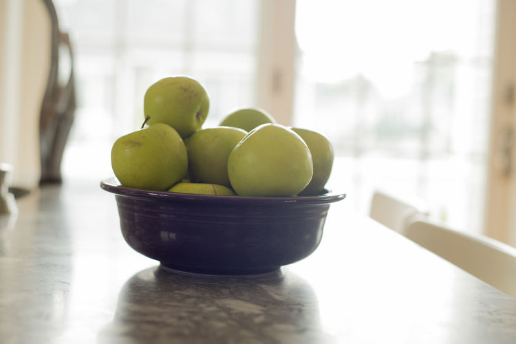Green apples in a bowl on a kitchen Apple Bowl Close-up Day Focus On Foreground Food Food And Drink Freshness Fruit Granny Smith Apple Green Color Healthy Eating Indoors  No People Selective Focus Still Life Sunlight Table Wellbeing Window