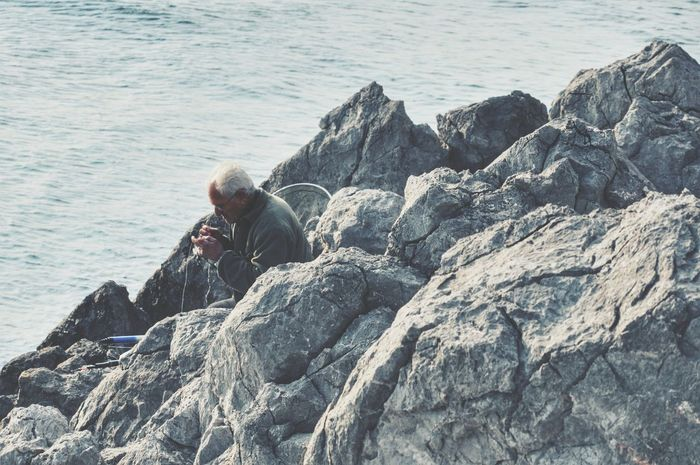 People Of The Oceans Fisherman By The Sea Sea And Rocks Coastline One Person Adult Outdoors Old But Awesome Fishing Time Capture The Moment Fishing Real People From My Point Of View Elderly Man Old Man Lifeisbeautiful Nikonphotography People Localscene The Human Condition - Greek Islands
