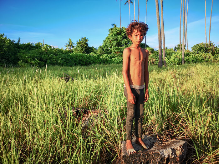 Unidentified faces of nomadic young sea gypsy ethnic pose for camera at the remote island called Maiga Sipadan in Semporna, Sabah, Malaysia. Shirtless One Person Nature Lifestyles Land Day Leisure Activity Real People Outdoors Plant Growth Standing Tree Sky Young Adult Field Green Color Grass Beauty In Nature Young Men Three Quarter Length Contemplation Shorts