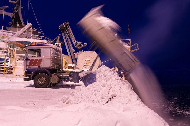 Truck dumping snow in lake
