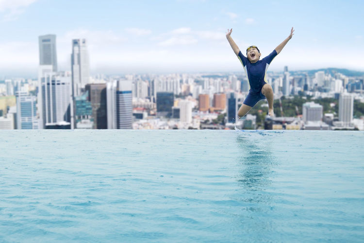 Happy boy with arms raised jumping in infinity pool against cityscape