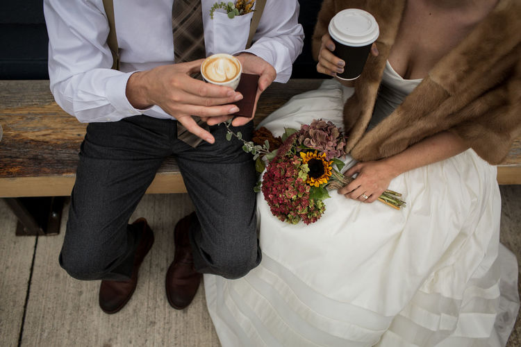 High angle view of newlywed couple holding coffee cups while sitting on bench