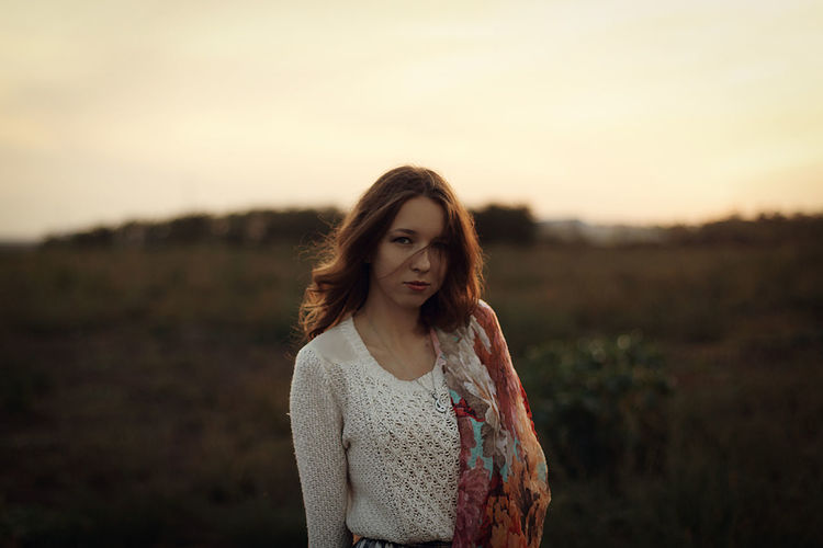 Portrait of young woman standing against sky during sunset