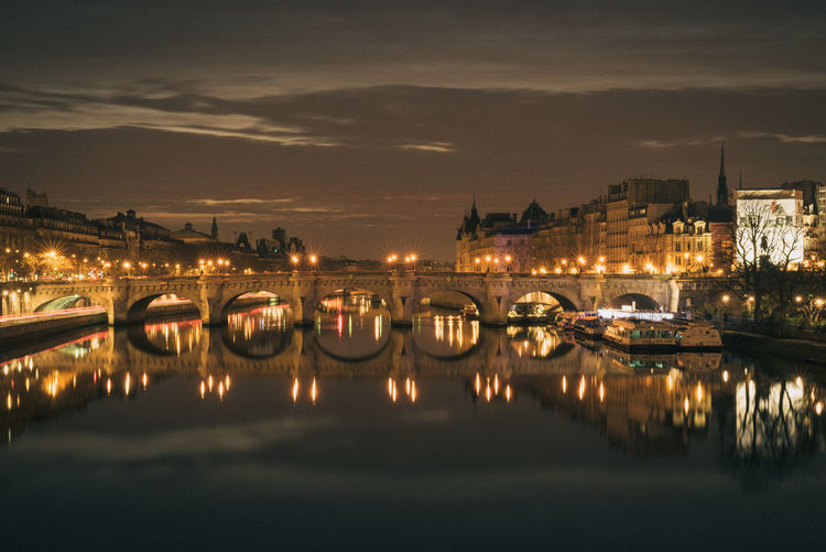 Illuminated pont neuf over seine river amidst buildings against sky at night
