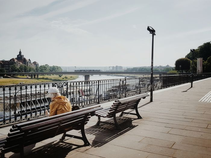 Man sitting on bench by elbe river against sky