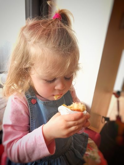 Child carefully eating a bun Eat Girl Food And Drink Child Childhood Girls Food Eating One Person Sweet Food Real People Holding Cute Lifestyles Sweet Innocence Dessert