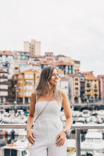 Young woman standing against cityscape in city against sky