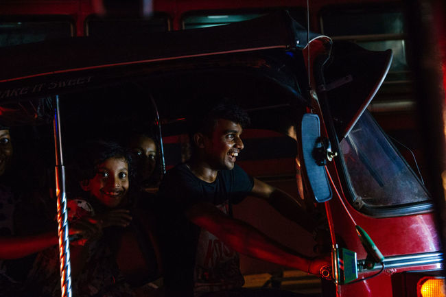 The streets were bustling and writhing with energy in Galle as Sri Lankans celebrated Vesak, the day of Buddah. Shooting from a Tuk Tuk in low light is extremely difficult in ever changing circumstances with light shifting every time traffic moves. Sri Lanka The Street Photographer - 2018 EyeEm Awards The Traveler - 2018 EyeEm Awards Car Commute Enjoyment Happiness Leisure Activity Lifestyles Looking At Camera Mode Of Transportation Motor Vehicle Smiling Transportation