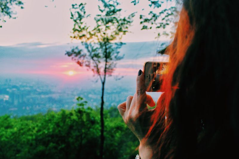 Rear view of woman photographing using phone against sky during sunrise