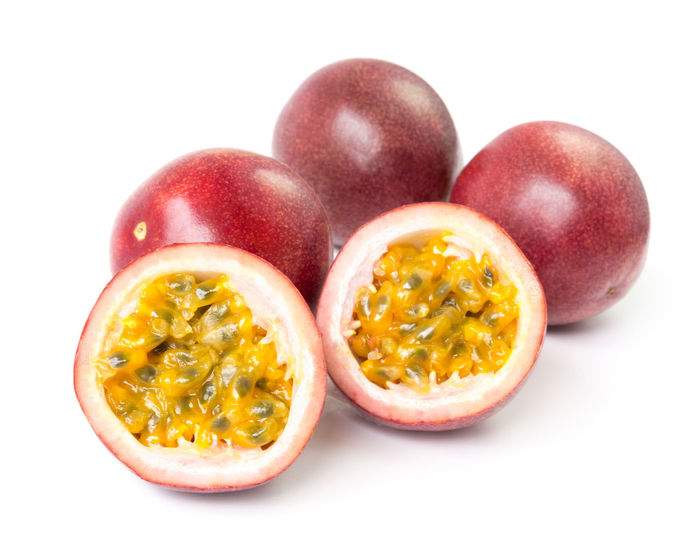 Closeup top view passion fruit on white background, fruit for healthy concept Diet Exotic Natural Pink Seed Dilicious Food Food And Drink Freshness Fruit Half Healthy Eating Healthy Food Ingredient Passion Fruit Ripe Season  Sweet Topical White Background Yellow