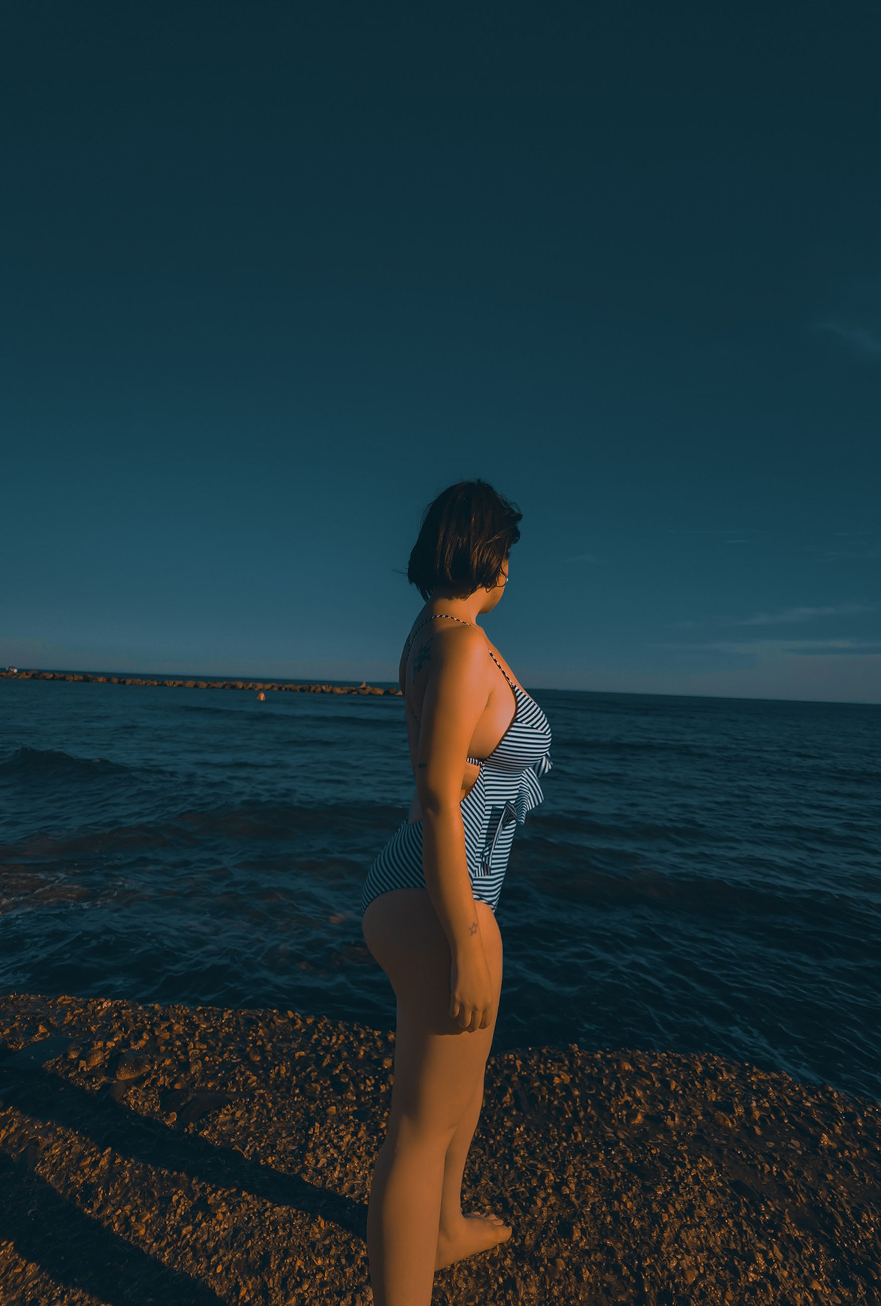 sea, water, one person, sky, horizon, land, beach, horizon over water, adult, women, nature, young adult, beauty in nature, ocean, standing, clothing, side view, full length, tranquility, sunlight, sunset, vacation, scenics - nature, holiday, hairstyle, trip, tranquil scene, lifestyles, leisure activity, blue, copy space, solitude, wave, person, outdoors, female, looking, contemplation, fashion, idyllic, relaxation, clear sky, summer, long hair, dusk, swimwear, sand