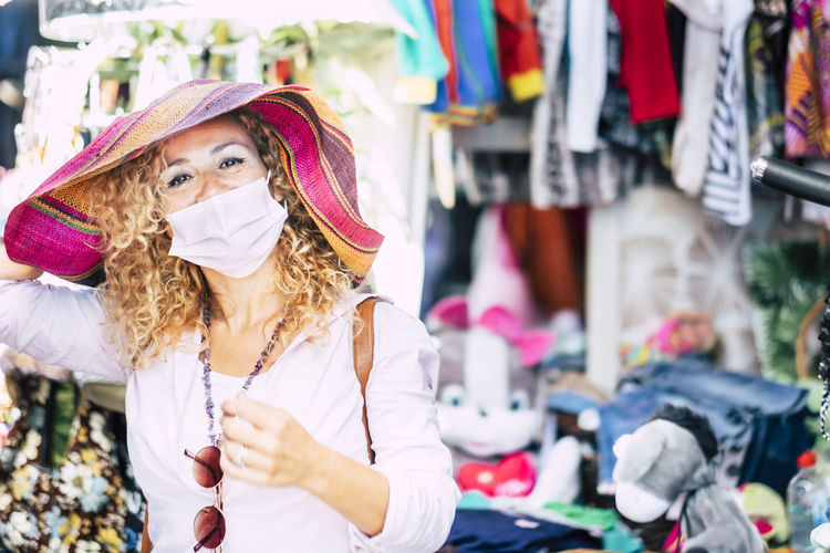 Portrait of woman wearing mask standing at market