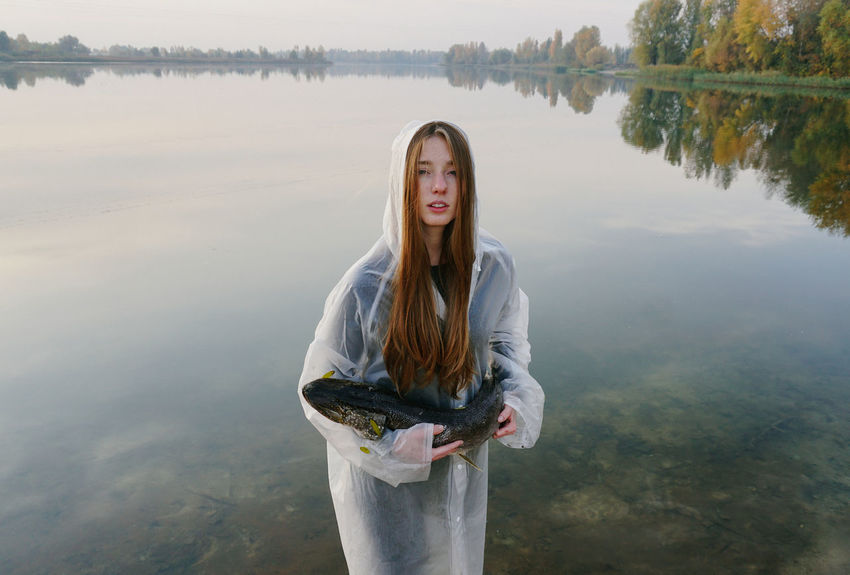 Fish Fishing Fisherman Nature Nature Photography Beauty In Nature Portrait Beautiful Woman Outdoors Hairstyle Lifestyles Real People Water Young Adult Looking At Camera Young Women Reflection Waterfront Lake Autumn Red Hair Redhead Girl Raincoat Trees