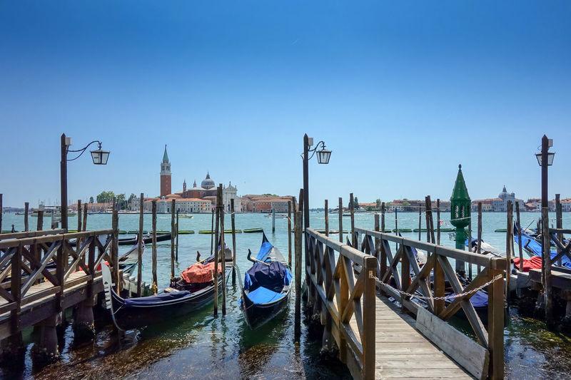 Gondolas moored on grand canal against clear blue sky