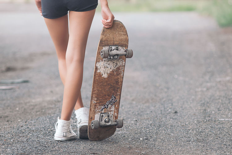 Low Section Of Woman Walking With Skateboard