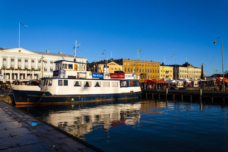 Passenger Craft At Port By Buildings Against Clear Blue Sky