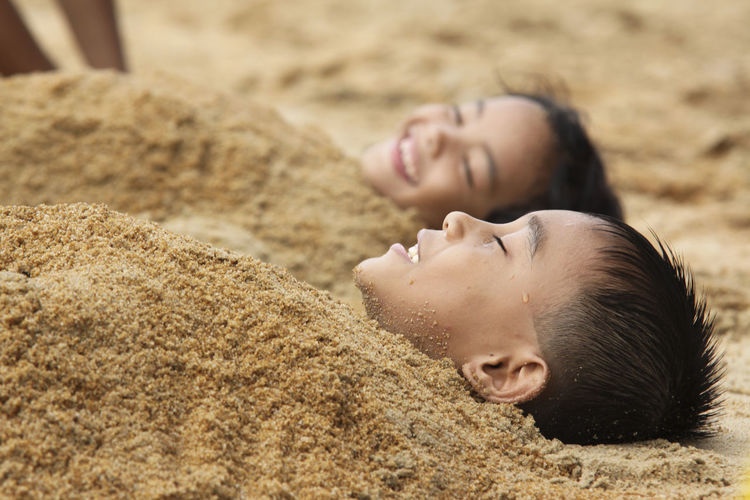 Close-up of playful siblings covered with sand