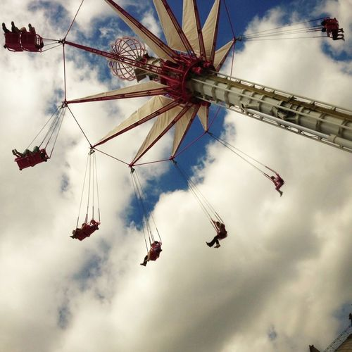 Low Angle View Of Chain Swing Ride Against Cloudy Sky